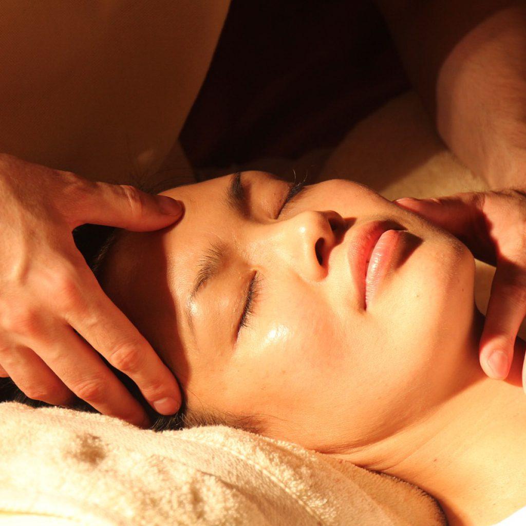 Curandero o sanador tradicional, masajeando la cara de una mujer.